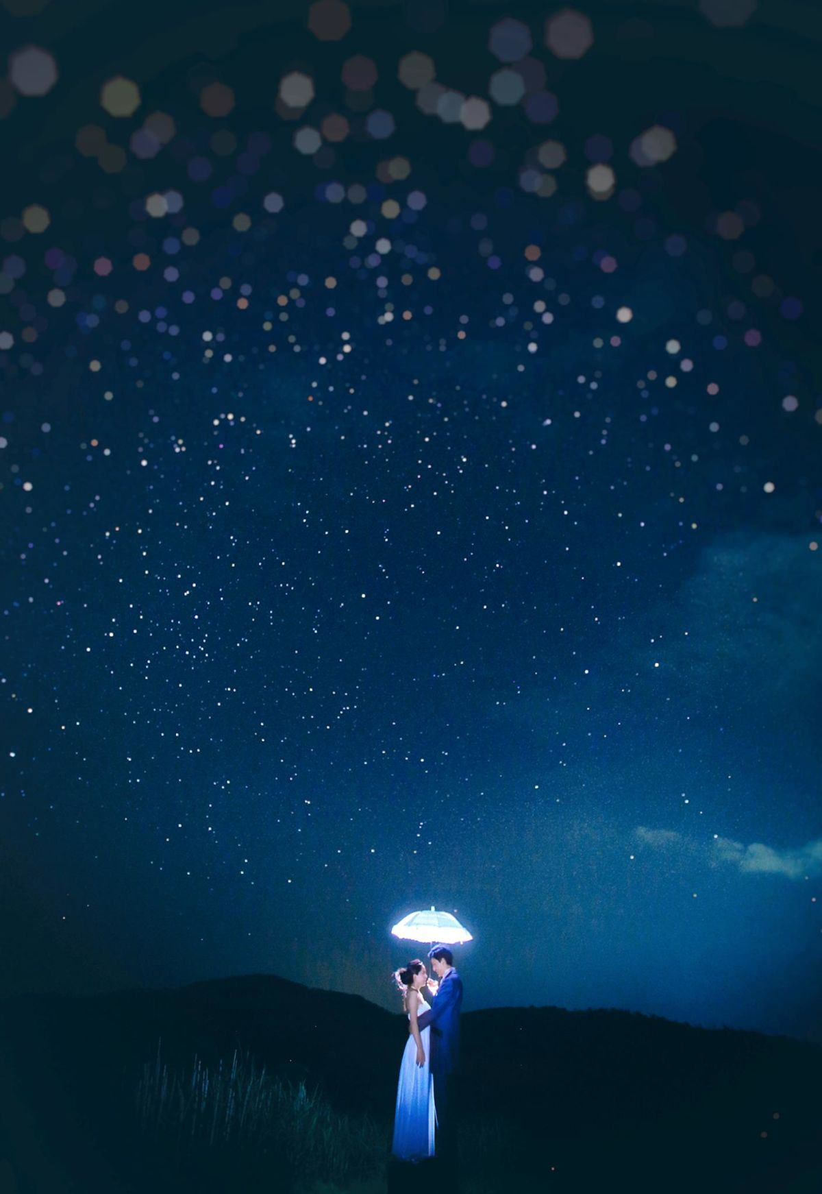A couple illuminated under the dazzling night sky — Photo by Ranmaru Style