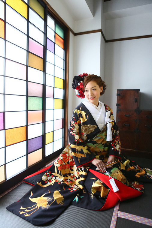 A bride wearing a black and gold hikifurisode