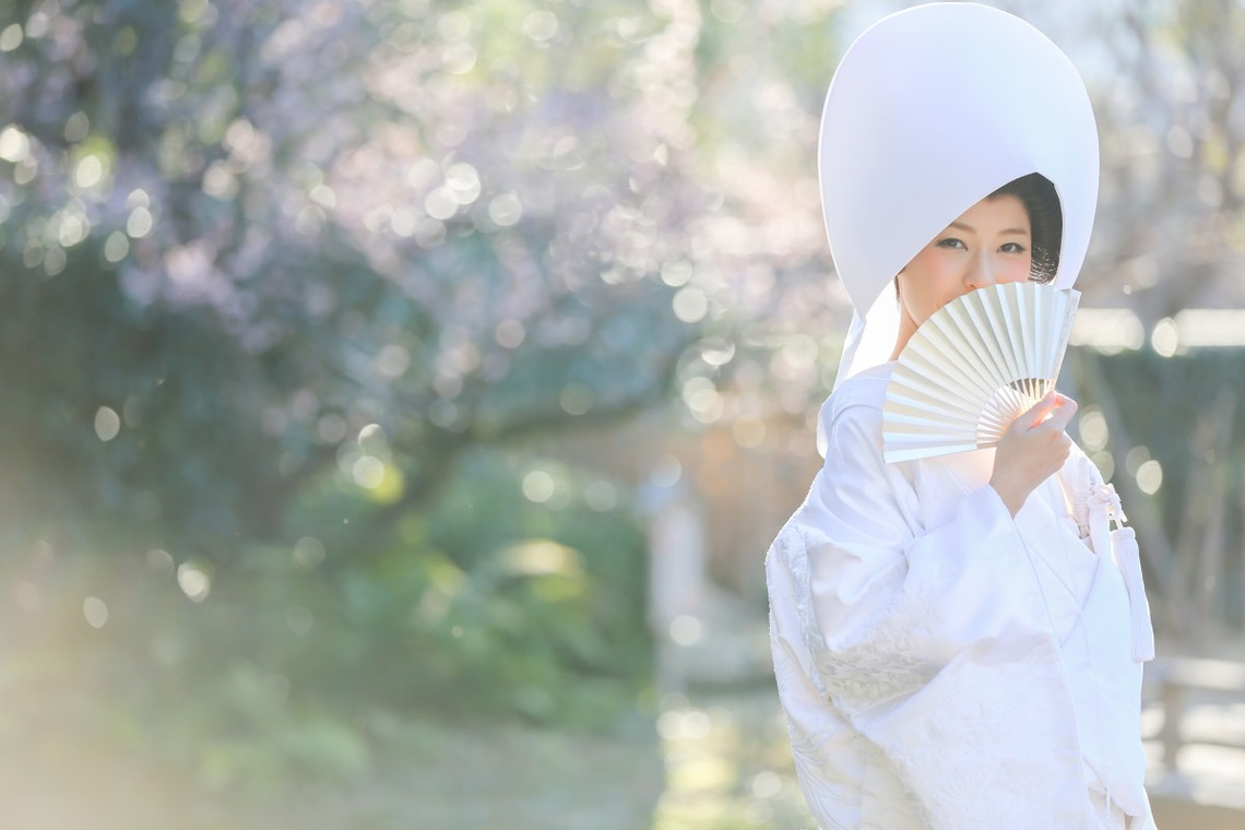 Lady wearing a shiromuku with an open hand fan