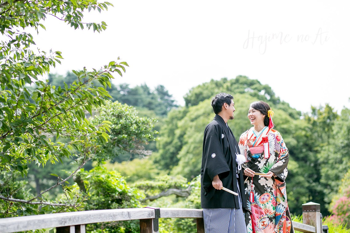 A couple in kimono on a wooden bridge in a park.