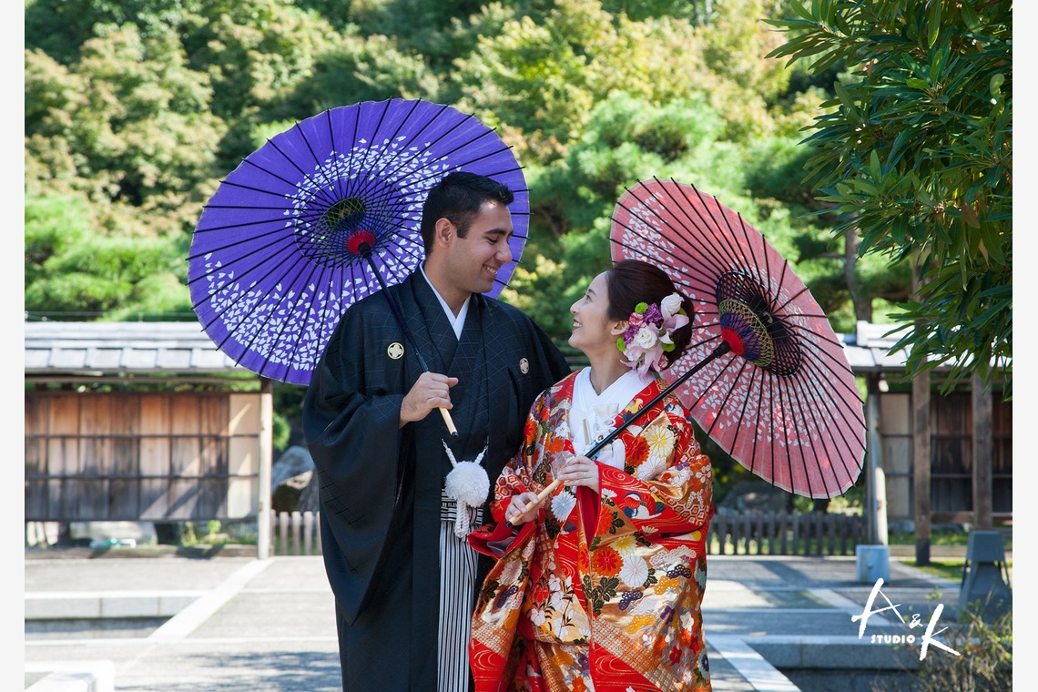 Kimono-dressed couple at a wooden Japanese gate.