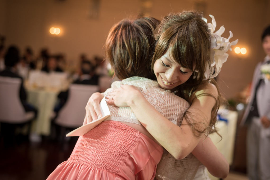 Bride hugging her maid of honor at the reception.