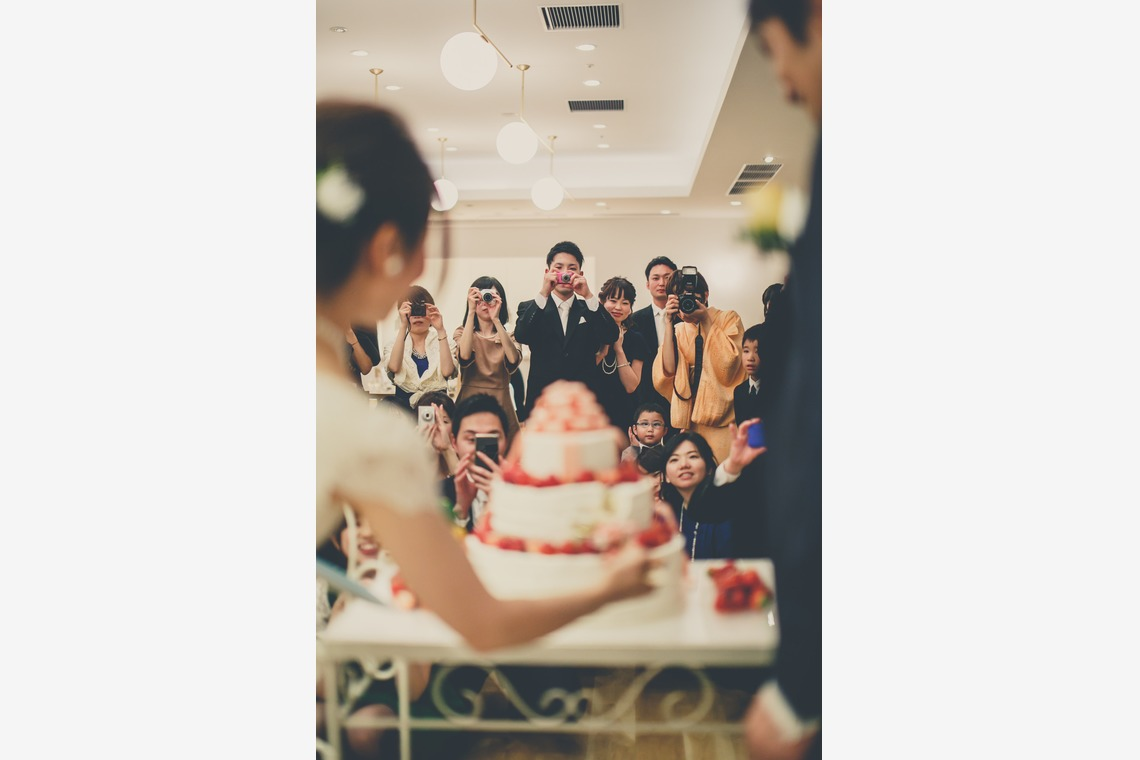 Couple cutting the cake, with guests watching