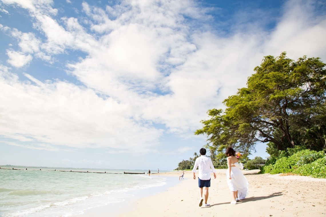 A couple walking along the beach in Hawaii — Photo by Kazuki Takano