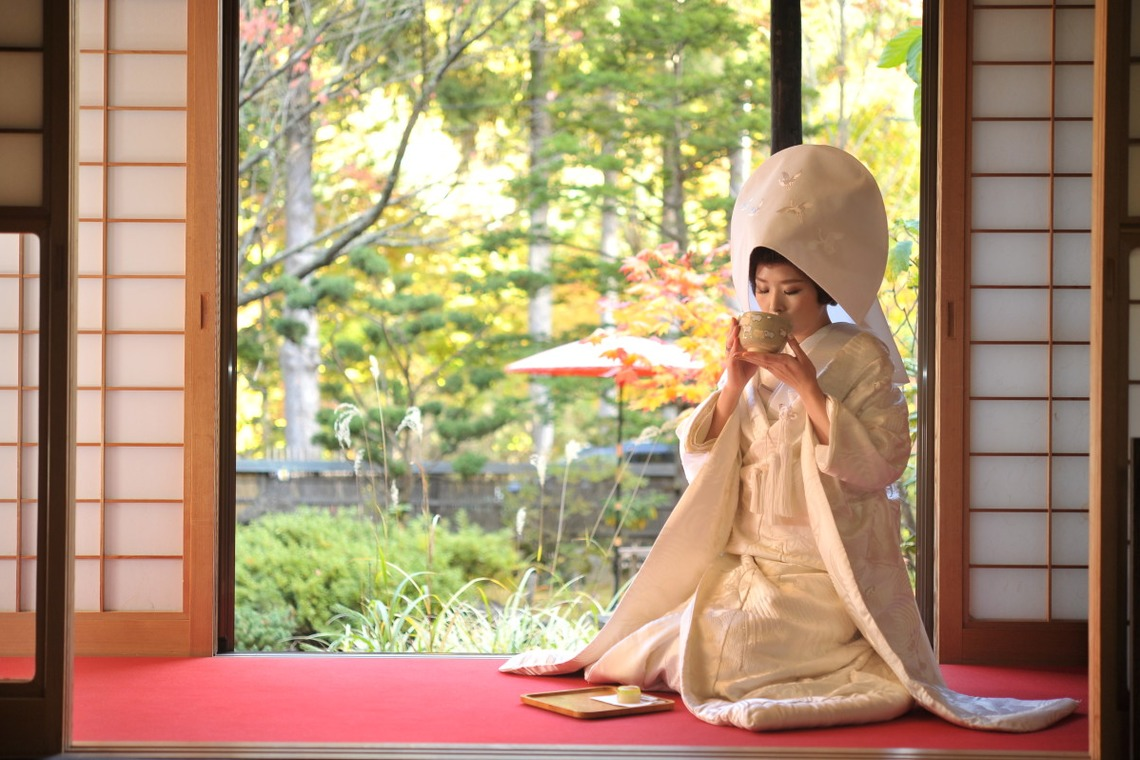 Lady in Shiromuku drinking tea next to a garden